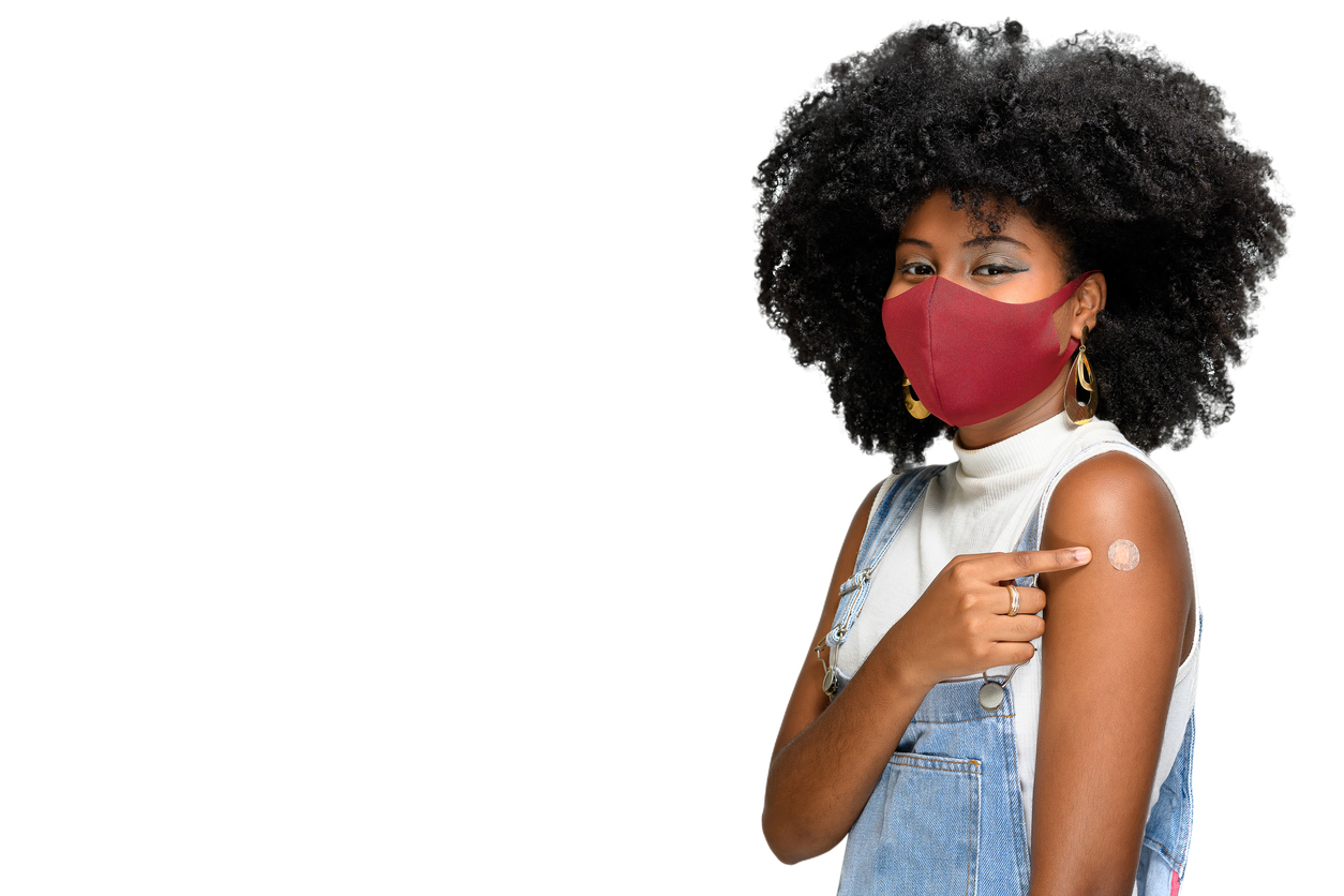 Woman in mask pointing to vaccine bandage